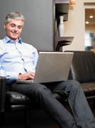Mature man sitting on sofa using laptop Stock Photos