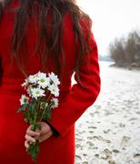 Young woman holding flowers behind back Stock Photos
