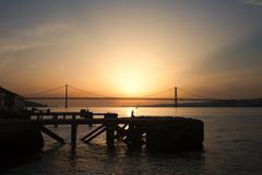 Sunset at Almada Quay and 25 de Abril Bridge in Lisbon Stock Photos