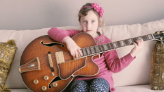 Portrait of young girl with a guitar sticking out his tongue Stock Footage