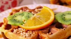 Belgian waffles with kiwi and orange pour syrup, topping, caramel, boiled Stock Footage