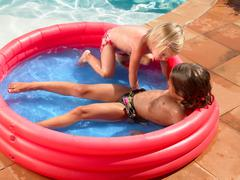 Two children playing in a kiddie pool Stock Photos