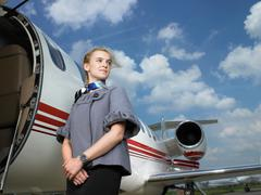Flight attendant beside private jet. Stock Photos