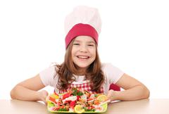 Happy little girl cook with seafood on table Stock Photos