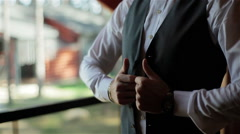 Stylish man in a suit and white shirt buttons vest waistcoat standing by window Stock Footage