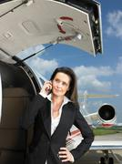 Businesswoman outside of private jet Stock Photos