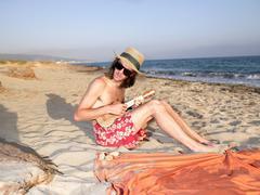 Man playing a ukulele at the beach Kuvituskuvat
