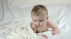 Laughing baby under a knitted cape on a white background - stock footage