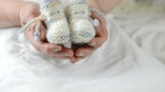 Grandma hands knitted socks, baby care - stock footage