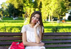 Beautiful girl sitting bench, brunette in a pink dress, fashion lifestyle Stock Photos