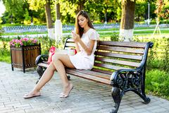 Beautiful girl sitting bench, brunette pink dress, fashion life style with your Stock Photos