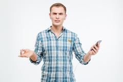 Unhappy irritated young man listening to music from smartphone Stock Photos
