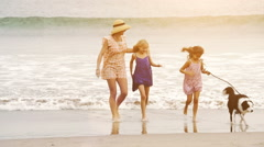Single mom and 3 daughters with a border collie walking along the beachfront  - stock footage