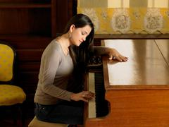 Young woman playing piano with one hand Stock Photos