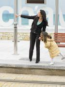 Woman and little girl waiting for tram - stock photo