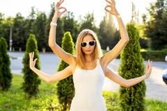 Two sisters playing summer park, having fun, doing yoga from the hand symbol - stock photo