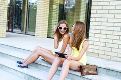 Two sisters steps of the institute laugh happy watching a movie  tablet in - stock photo