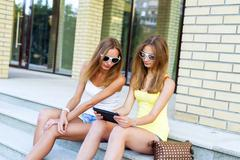 Two sisters steps of the Institute watching a movie on tablet in social networks - stock photo