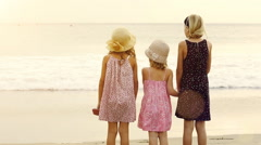 3 sisters standing on sea shore beach looking out at the ocean. - stock footage
