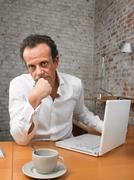Pensive businessman sitting at desk - stock photo