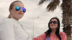 Two women friends in sunglasses of the talking at the bench - stock footage