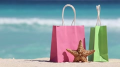 Shopping bags and starfish on sand against turquoise caribbean sea water Stock Footage