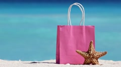 Pink shopping bag and starfish on sand against turquoise caribbean sea water Stock Footage