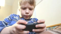 Funny 8 years old kid playing computer games laying in his bed in morning Stock Footage