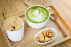 White cup  of green tea on a wooden tray with a snack - stock photo