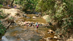 People traveling in stream of the creek in forest at Mae Sa Noi waterfall. Stock Footage
