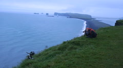 Girl photographs  puffins  in Dyrholaey, Iceland Stock Footage