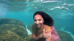 Young beautiful woman in dress posing submerged under water on coral feef - stock footage