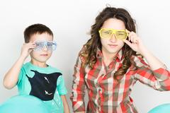 brother and sister, wearing glasses in the style of disco. fold one's arms - stock photo