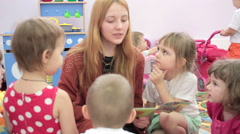 Storytime - a elementary school teacher reading a story to a group of children Stock Footage
