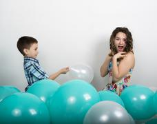 Brother kisses his sister around them lie balloons - stock photo