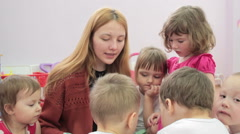 Storytime - a kindergarten teacher reading a story to a group of children Stock Footage