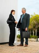 Businesspeople by a silver wall. Stock Photos