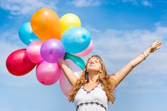 Happy young lady celebrates birthday and playing with balloons Stock Photos