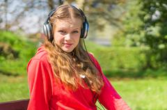 Young lady listening to music and relaxing on a park bench - stock photo