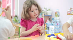 Little girl playing doctors in kindergarten with other children. - stock footage