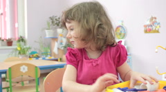 Little girl playing doctors in kindergarten with other children. Stock Footage