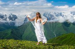 Grassy valley, snowy mountains and beautiful dancing girl in white wedding dr - stock photo