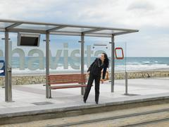 Young businesswoman waiting at tram stop - stock photo