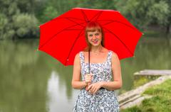Beautiful young lady with red umbrella near the pond - stock photo