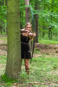 Young lady Elf with a long bow in the wild forest - stock photo