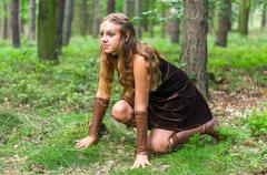 Young lady Elf with a long bow in the wild forest Stock Photos