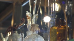 Glass movement in slow motion along glass bottles and old lamps Stock Footage