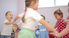 Kids playing running around dancing in kindergarten and laughter - stock footage