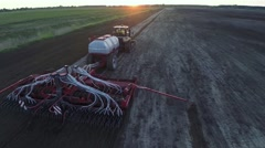 Aerial drone shot of a combine harvester working in a field at sunset - stock footage