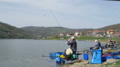 Group of fishermen are competing on the lake, fishing by Pakito. Stock Footage